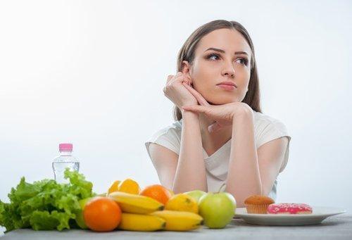 cibi alcalini: ragazza con verdure pensierosa