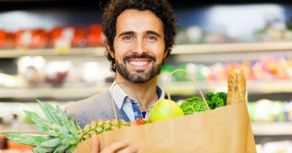 ragazzo fa la spesa con verdure fresche e surgelate