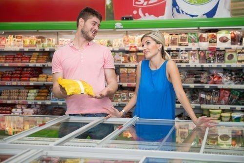 coppia sceglie le verdure surgelate al supermercato