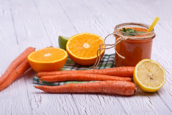 orange detox coctail with oranges and carrots lies on white tabl