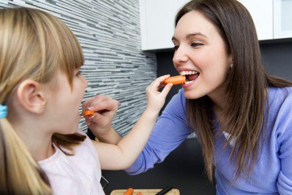 mamma e figlia con carota come spazzolino